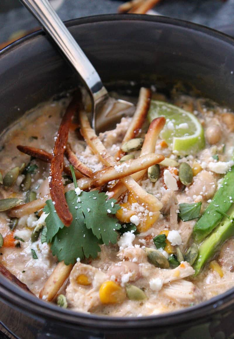 Slow Cooker White Chicken Chili ~ creamy, loaded with chicken, beans, corn and green chilies. Topped with avocado, lime wedge and tortilla strips.