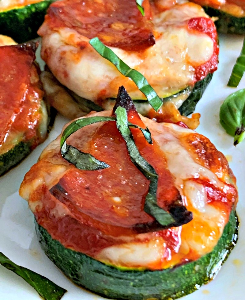 zucchini pizza bites on white plate garnished with sliced basil